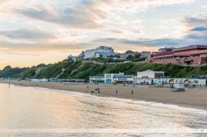 Le soleil se couche derrière les falaises surplombant la plage