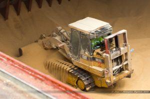 Tractopelle en action dans la soute du Rosco Palm remplie de tourteaux de soja