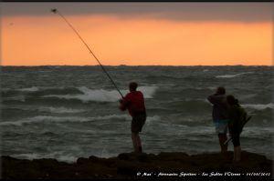 Pêcheurs à la ligne en action sur les rochers de la plage de l'Aubraie